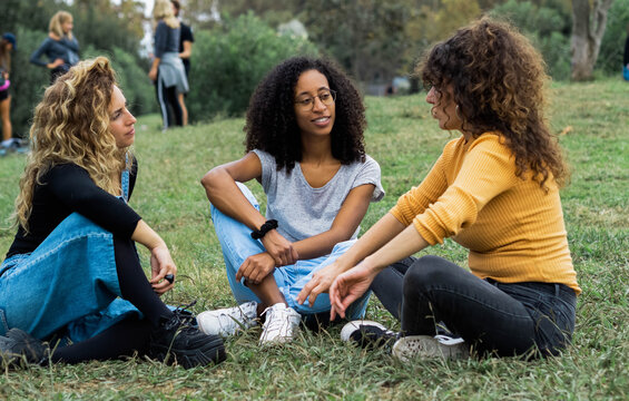 Company of diverse female friends sitting on lawn in summer park and talking to each other