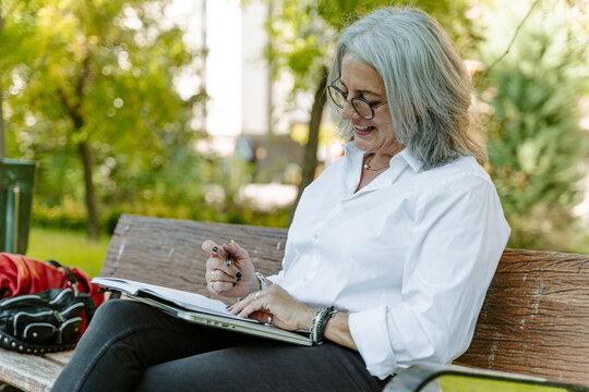Side view of middle aged female entrepreneur in smart casual wear sitting on bench and writing list of daily routine tasks while working remotely in park