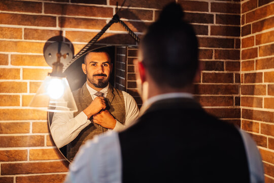 Back view of confident bearded masculine man in formal clothing adjusting tie and looking at reflection in mirror