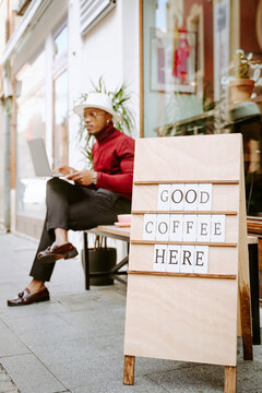 Wooden board with inscription Good Coffee Here placed near coffee shop on background of black male freelancer working on laptop on bench