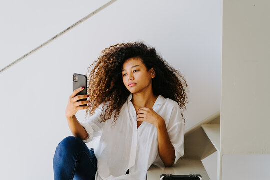 Young ethnic curly haired female in casual white blouse and jeans taking self portrait on mobile phone while sitting on stairway at home