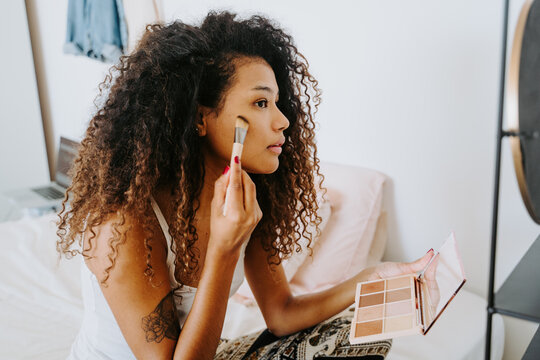 Side view of young curly haired ethnic female applying blush from palette on cheek with cosmetic brush during daily makeup procedure at home