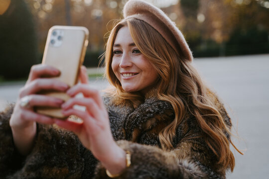 Charming female in beret and warm coat standing in park and taking selfie on smartphone while smiling and enjoying weekend