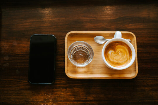 Top view composition with modern mobile phone placed on wooden table near tray with cup of cappuccino and glass of fresh water