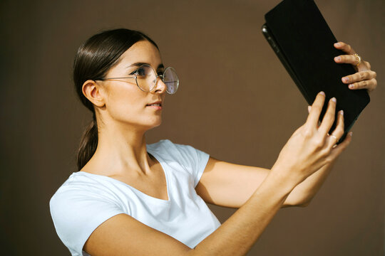 Side view of charming female standing in studio on beige background and taking selfie on tablet camera