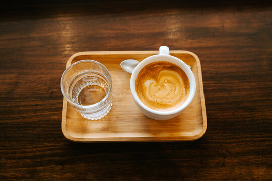 Top view composition of wooden tray with cup of cappuccino and glass of fresh water placed on wooden table