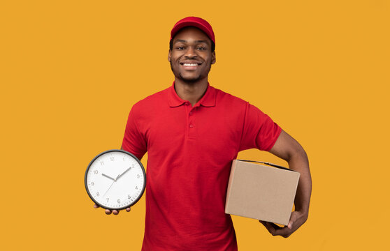 Smiling black delivery man holding box and clock