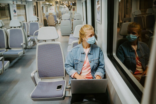 Concentrated female freelancer in medical mask browsing laptop while traveling by train