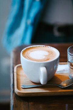 White ceramic cup with fresh hot aromatic cappuccino with heart shaped latte art served with spoon on wooden tray on table
