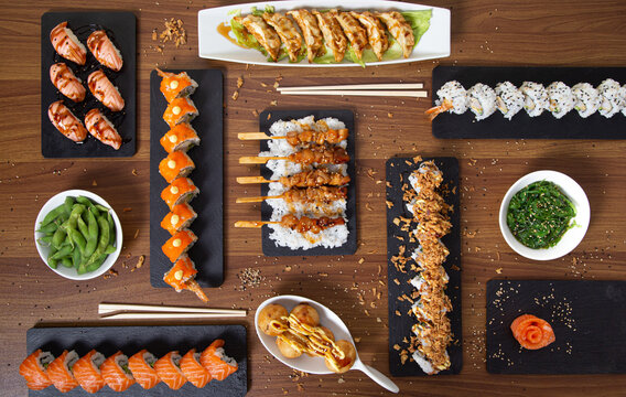 Top view of assorted sushi and rolls arranged on wooden table in restaurant with Asian food