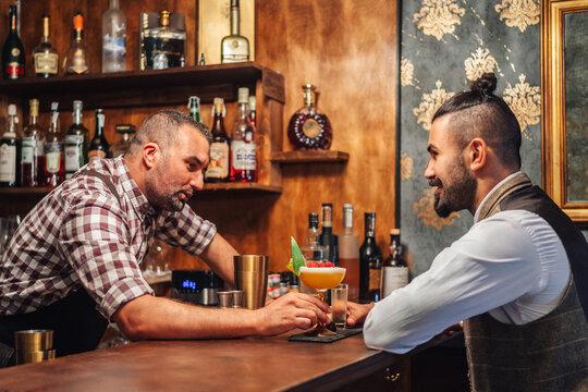 Side view of middle aged barkeeper giving cocktail with raspberries to elegant bearded man while working in bar