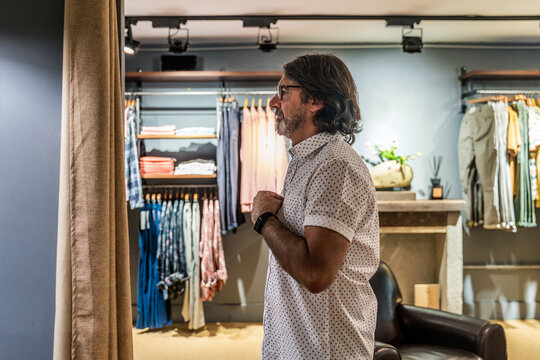 Side view of satisfied man looking at himself in the mirror of a clothing tester in a clothing store