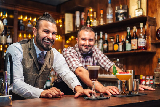 Bearded bartenders smiling while holding glasses of fresh cold sour cocktails at counter in bar