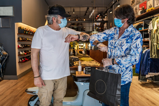 Side view of clothing store owner bumping elbows with customer after shopping while wearing face mask