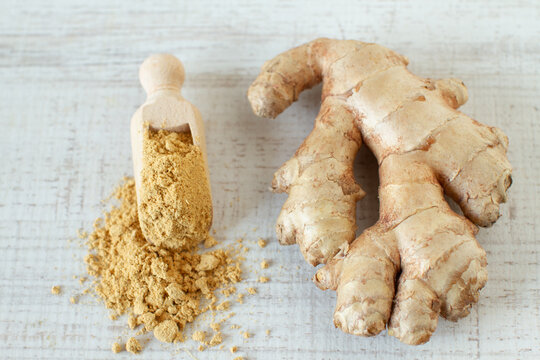 Fresh and ground ginger root spice on wooden table