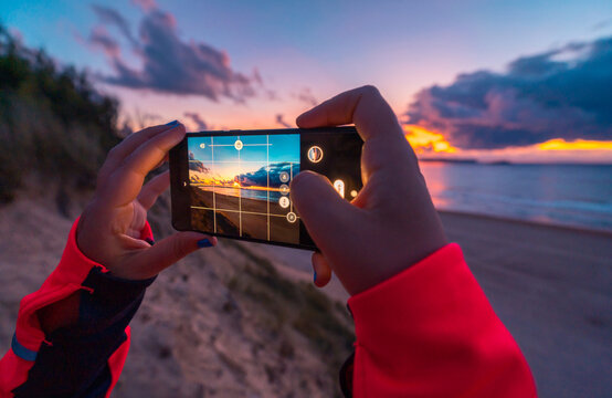 Back view of unrecognizable female traveler with long dark hair in casual clothes taking picture of amazing sunset over sea with sandy beach on smartphone during holidays in Cantabria