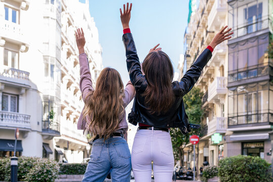 Back view of carefree female friends standing on street with raised arms and enjoying weekend on sunny day together