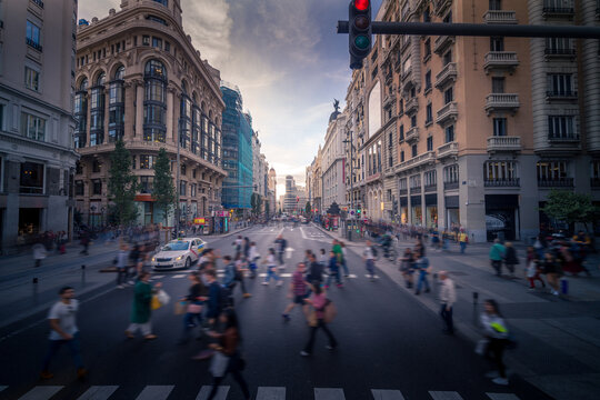 Crowd of blurred unrecognizable pedestrians walking on crosswalk in Madrid city in evening
