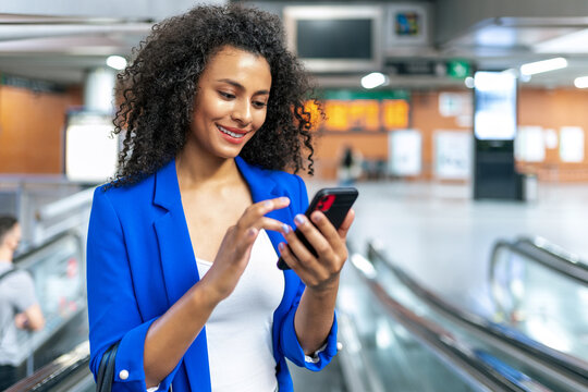 African American female in casual clothes standing in modern escalators and surfing Internet on smartphone