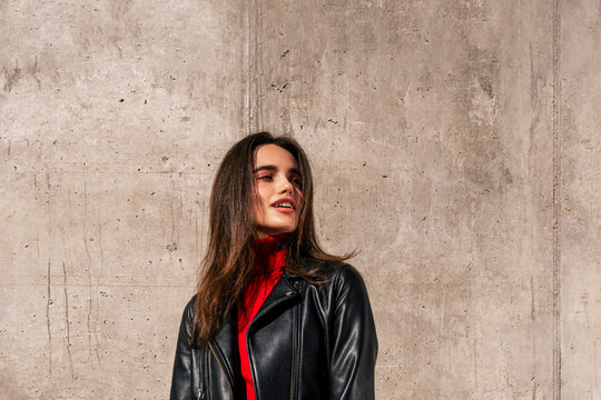 Young female model in black leather jacket and white jeans standing on street and confidently looking away