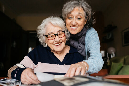 Cheerful senior mother and mature daughter sitting at table and looking through old photos from album together