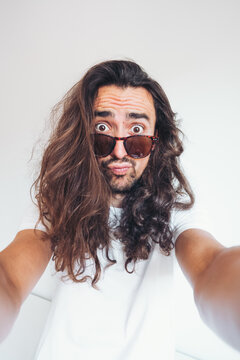 Young hipster long haired bearded male in sunglasses with funny amazed face expression looking at camera while taking selfie