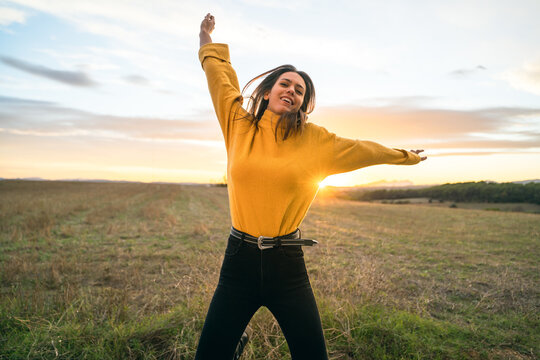 Carefree female in casual outfit in moment of jumping above ground in meadow on background of sunset in rural area