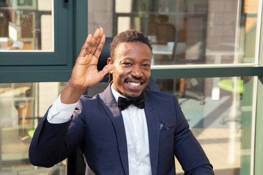 Cheerful adult African American male entrepreneur in elegant formal suit with bow tie looking at camera and waving hand while sitting against glass wall in modern office