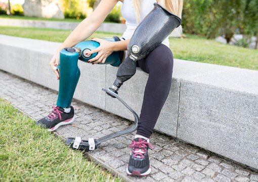 Unrecognizable crop female runner changing leg prosthesis for training while sitting on stone border in urban park