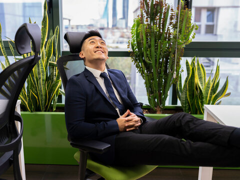 Side view of cheerful young Asian businessman in formal suit looking up and smiling dreamfully while thinking about successful business strategy in modern workspace