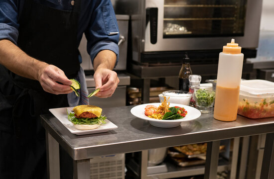 Crop unrecognizable male cook adding sliced fresh cucumber to hamburger with meat cutlet and cheese while preparing snack in restaurant kitchen