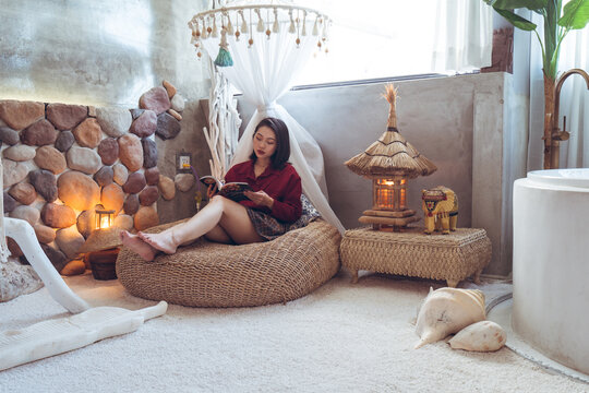 Full body of calm young Asian female traveler in casual clothes sitting on wicker pouf in stylish room with stone walls and typical oriental decorations while chilling in hotel in Taiwan