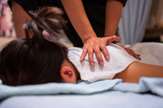 Crop unrecognizable masseur putting white towel on client covered with blanket while doing rehabilitation massage in professional salon