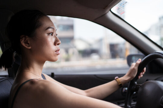 Side view of focused Asian female driving modern automobile along road in Taichung city