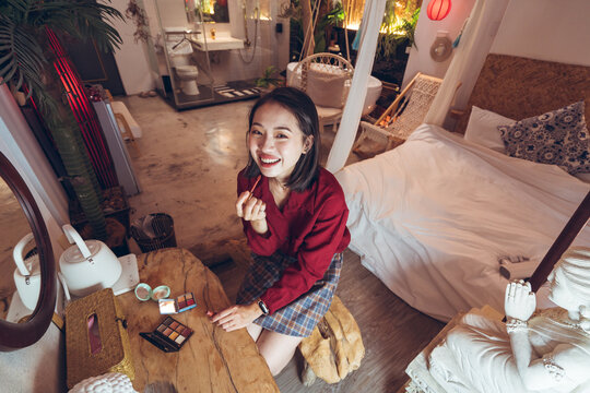 Young Asian female applying red lipstick while standing in front of mirror in room with traditional oriental interior