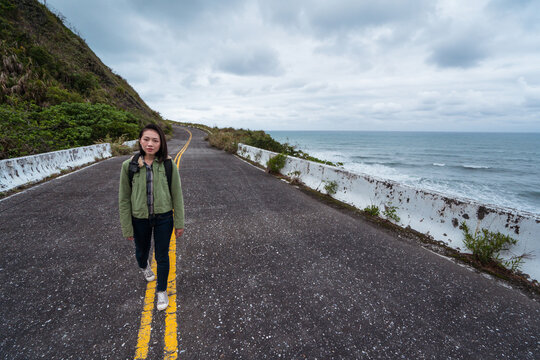 Active female hiker with backpack walking on asphalt road leading along rocky coast in stormy weather with waving sea looking at camera