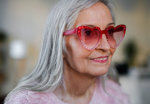 Portrait of happy senior woman with party sunglasess standing indoors at home.