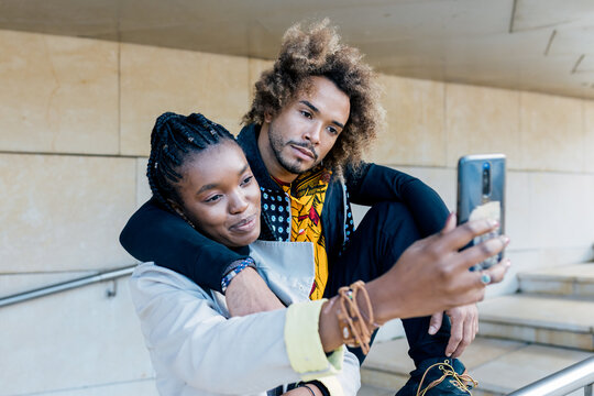Cheerful young African American couple hugging and taking selfie on smartphone while spending time together in city