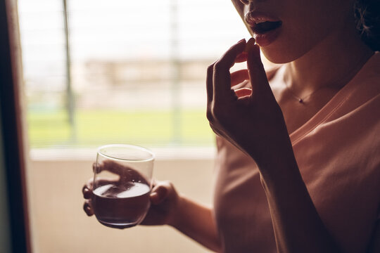 Crop unrecognizable female with glass of fresh water taking yellow vitamin pill while representing healthy lifestyle concept