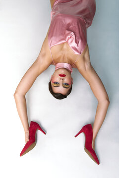 From above of fashionable female model with bright makeup wearing pink dress holding stylish red high heeled shoes in hands while lying on white floor