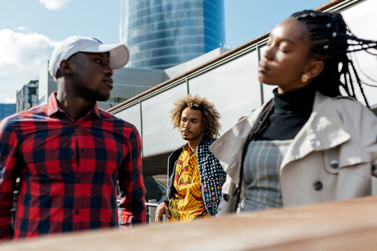 Unhappy young black man suffering from unrequited love while girlfriend having serious conversation with other guy on city street
