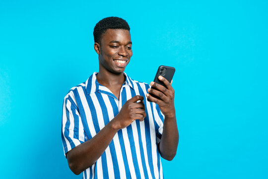 Delighted African American male browsing smartphone and reading good news about business project while standing with clenched fist on vivid blue background in studio