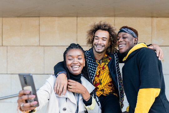 Cheerful young African American hipster guys hugging smiling girlfriend while having fun together on stairway taking selfie with smartphone in city