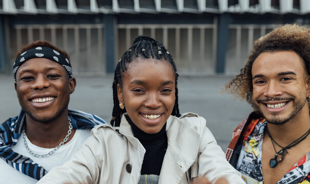 Group of cheerful young African American hipster friends in trendy outfits looking at camera and smiling happily while taking selfie together on urban street
