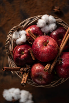 Top view of pile of wet red apples and cotton flower placed in wicker basket on rustic table
