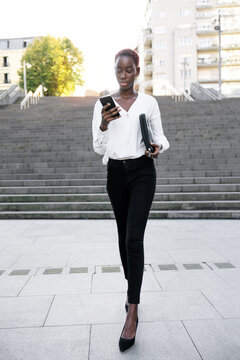 Young African American businesswoman in classy outfit reading message on smartphone while standing on stairway on urban street