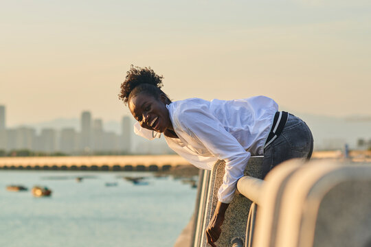 Side view of happy laughing young African American female in casual wear leaning over fence and looking at camera while enjoying free time on urban seafront