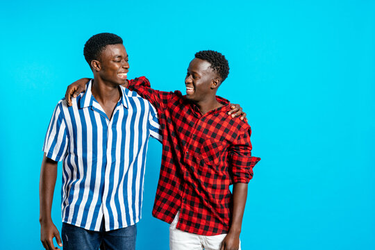 Cheerful African American male friends in stylish outfit standing together on blue background in studio and looking at each other