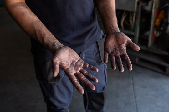 High angle of crop unrecognizable male mechanic showing dirty hands while working in repair service workshop