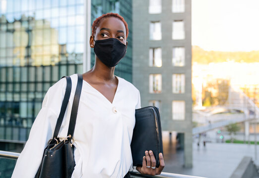 Serious stylish young African American business lady in white blouse and black protective mask for coronavirus prevention holding case with laptop while standing against contemporary glass building in modern city district